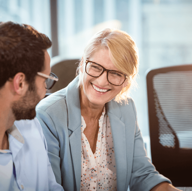 Smiling woman sitting with colleague using transformational leadership skills in the workplace